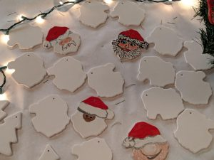 a variety of santa claus ornaments are displayed on a table
