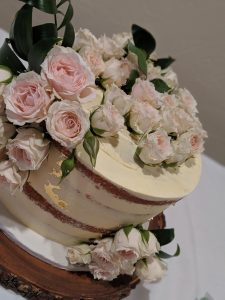 Wedding Cake with Pink Flowers on a Wood Slab
