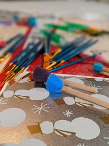 paintbrushes are splayed across holiday wrapping paper
