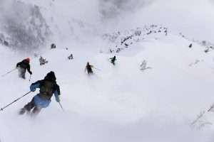 Skiers descend a mountain into infinite powder