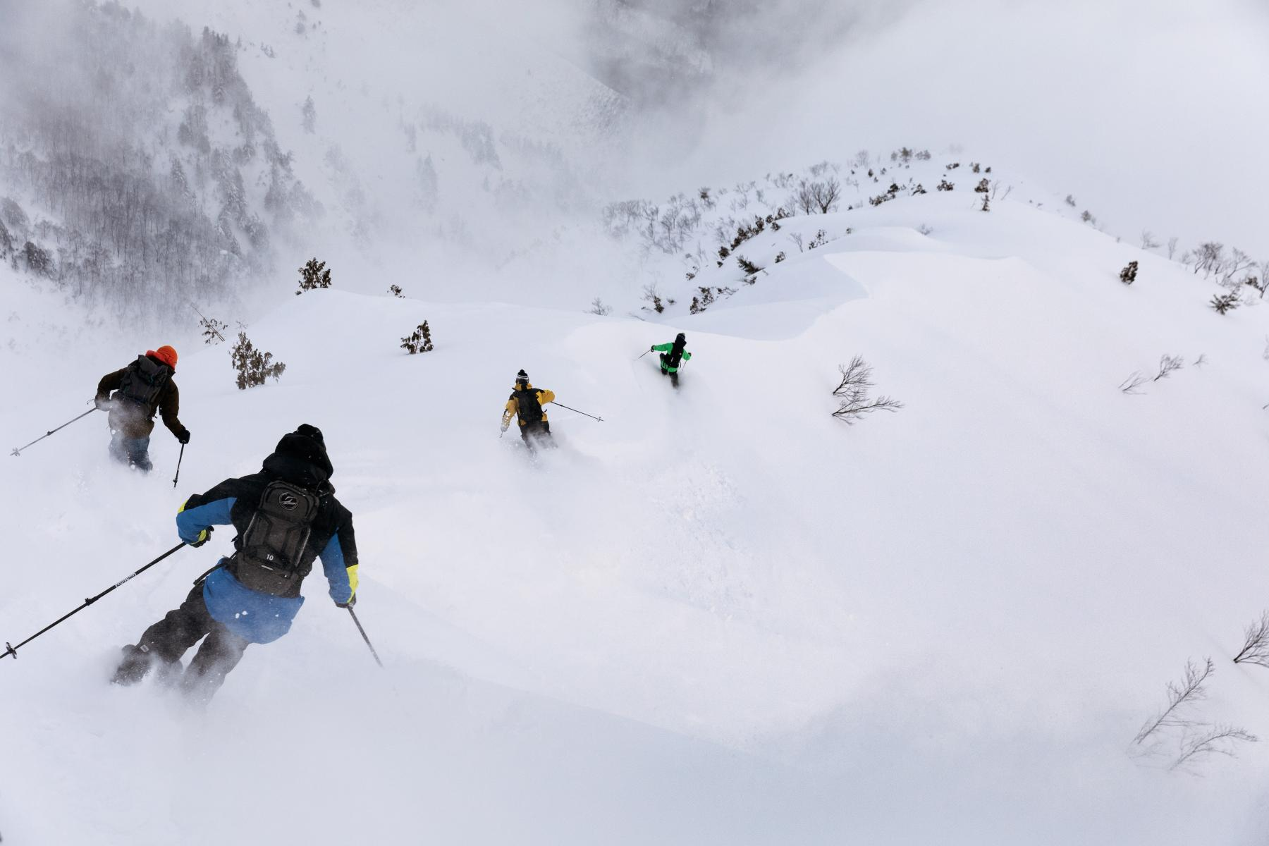 Skiers descend a mountain into infinite powder