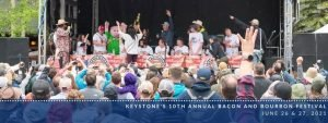 Onlookers cheer for the annual Bacon Eating Contest at Bacon and Bourbon Festival
