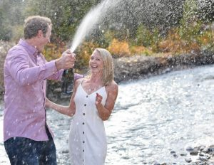 Chelsea and Brett stand under the spray of champagne next to a river
