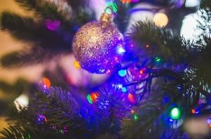 an ornament on a tree is lit up by the glow of blue lights