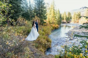 a woman in a wedding dress and a man in a suit overlook the snake river with yellow leaves in the background