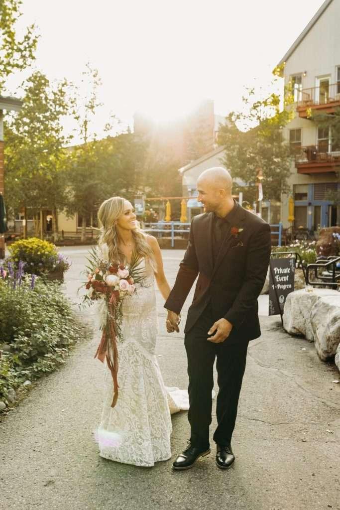 Bride and Groom Walking in River Run Village, Smiling
