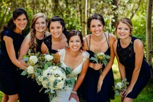 Wedding Party Standing In Greenery Smiling