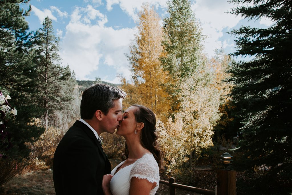 a bridge and groom kiss in front of the evergreen trees and yellow aspens of fall in Summit County