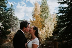 a bridge and groom kiss in front of evergreen trees and yellow aspens