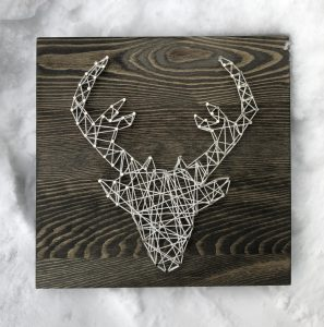 string art on a wooden background forms a deer head with antlers featured in the Speaker and Spirits Series