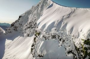 a professional skier drops a cliff on a snow covered peak