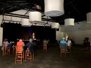 guests sit at tables spread 12 feet apart at a comedy show during COVID-19 at warren station