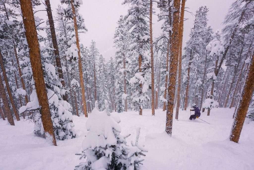 a skier in snowy glades at Keystone