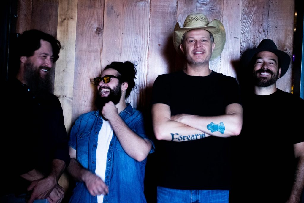 Jason Boland and the stragglers post in front of wood paneling