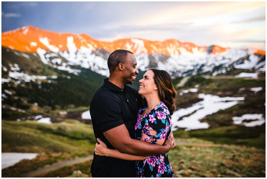 a couple embraces on top of loveland pass with snowy mountains and orange alpenglow in the background