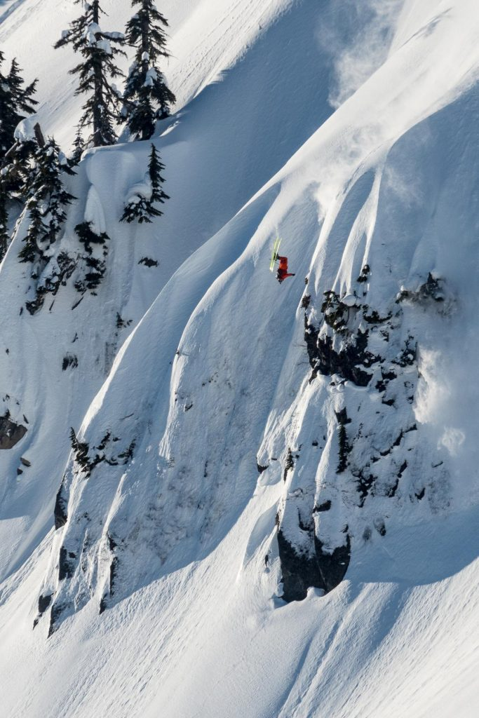 a skier front flips off of a huge snowy mountain
