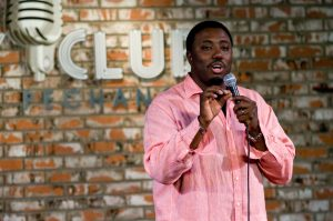 comedian louis johnson performs stand up comedy in a pink button down shirt