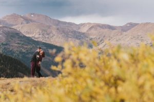 a couple kisses on top of loveland pass with mountains in the background and yellow willows in the foreground