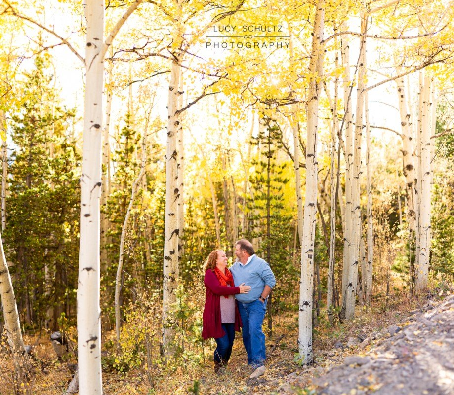 a couple taking fall engagement photos hug each other lovingly under a canopy of yellow aspen leaves on boreas pass