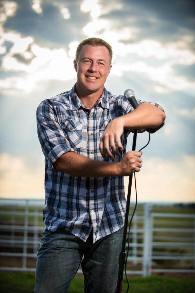 comedian talon saucerman leans against a microphone stand in front of a farm fence