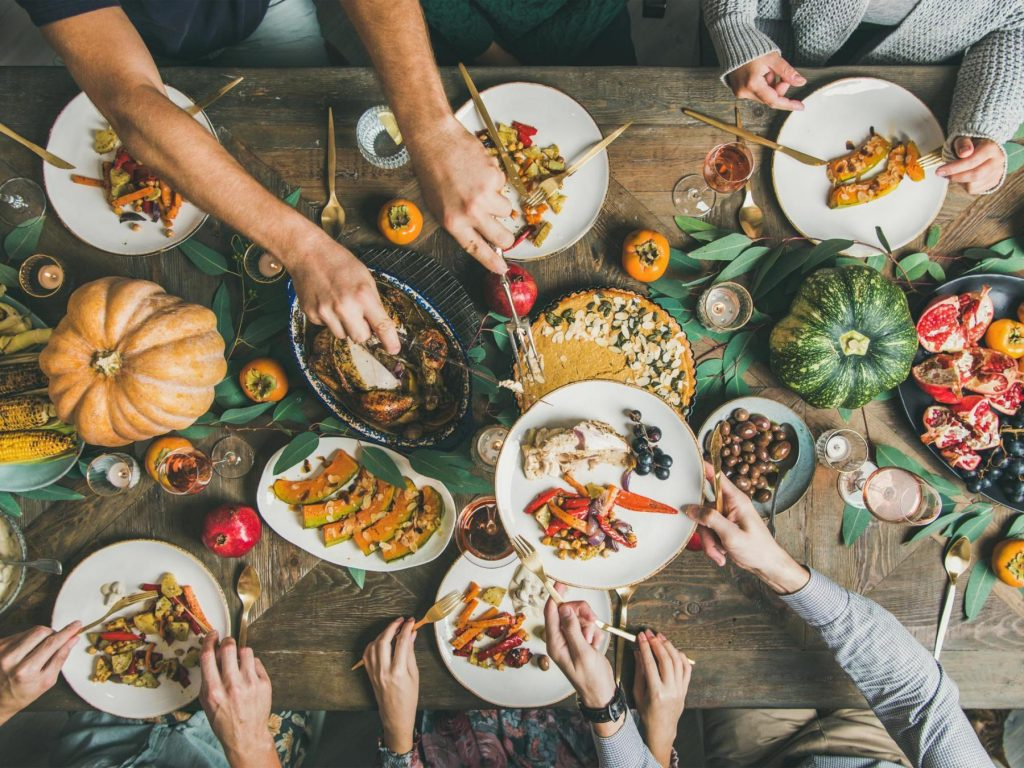 an overhead view of a thanksgiving feast laid out on the table as hands pile plates of food
