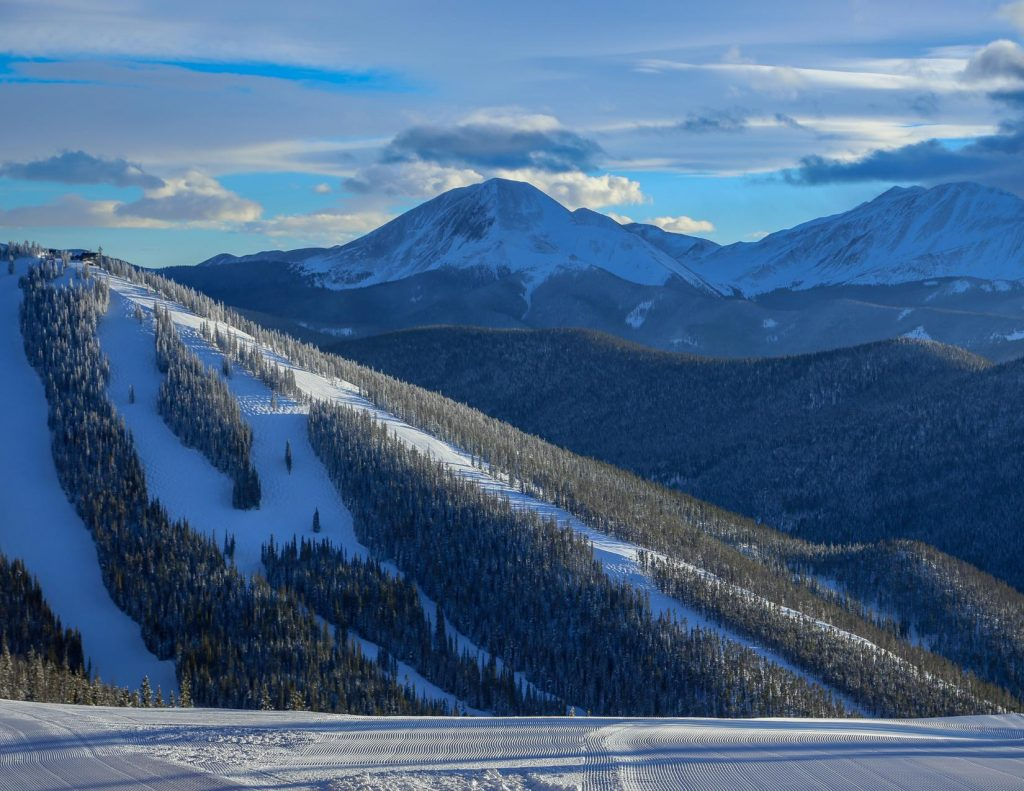 A view of North Peak at Keystone Ski resort with snowy mountains in the background