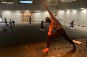 a yoga instructor leads the class in extended side angle pose