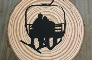 a woodburnt coaster shows the silhouette of two skiers riding a lift and is one craft you can pick at the event