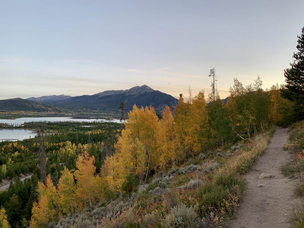 Orange aspens line an outdoor recreational hiking path with views of the Ten Mile Range in the background