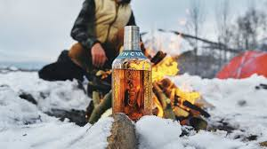 Pictured is a Tincup whiskey bottle in front a fire in the Colorado landscape. This Whiskey is featured in the Speaker and Spirits Series