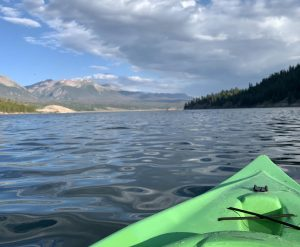 A green kayak rests on the surface of Lake Dillon with views of the Gore Range in the background