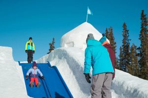 A child rides down a slide to her parents in the world's largest snow fort in Keystone Colorado
