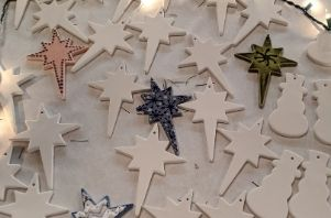 ceramic star-shaped ornaments by ready paint fire are laid out on a table, some painted some unpainted