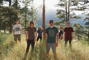 Boulder band Policulture poses in a clearing in a forest