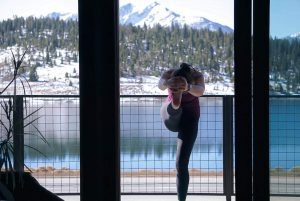 Yoga Instructor practices standing head-to-knee pose in front of lake dillon