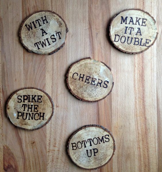 "coasters with wood-burnt phrases on them; ""cheers!"" ""bottoms up!"""